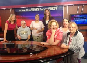 A happy group posing for pictures in the newsroom of local ABC affiliate KMIZ